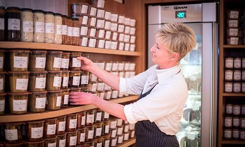 Mitarbeiterin füllt Frischeregal mit Produkten auf
